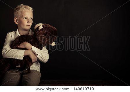 Boy Holding Large Plush Toy Over Black Background