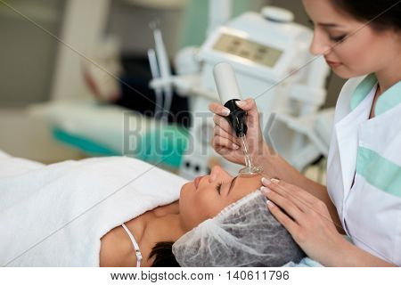 Professional cosmetologist undergoing darsonvalization on skin of face, skin and body care at beauty salon