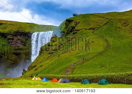 Grand waterfall Skogafoss. Near a waterfall put some colorful tourist tents.