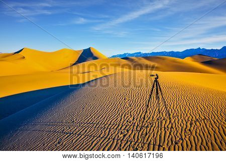 Tripod with camera stands on sand dune. Mesquite Flat Sand Dunes. Bizarre twists of orange sand dunes