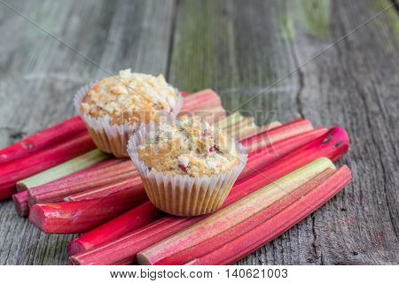 Two Rhubarb muffins on a rhubarb perioles on Old Wooden Board