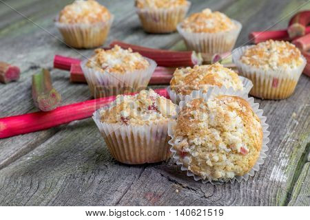 Rhubarb muffin with rhubarb petioles in the background on Old Wooden Board
