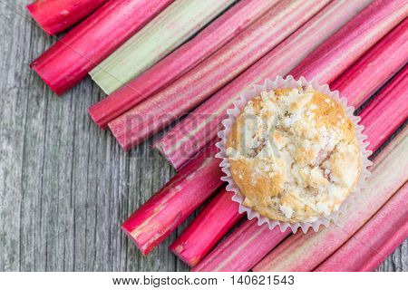 Top View on Rhubarb muffin on a rhubarb perioles on Old Wooden Board
