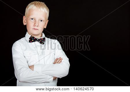 Unsmiling Boy With Arms Crossed And Dotted Bow Tie