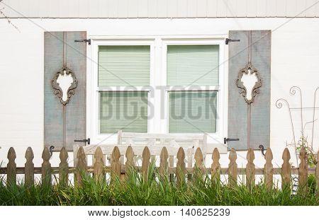 Woody grey ornamental shutters on a window