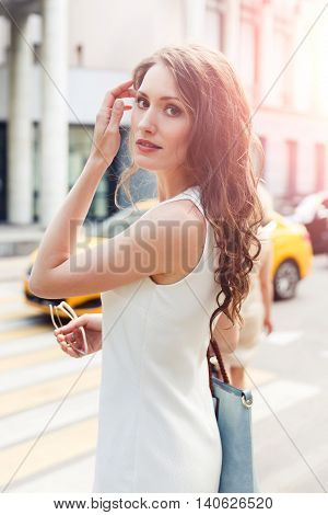 Young lady with curly brunette hair crossing the road. Image with lens flare effect