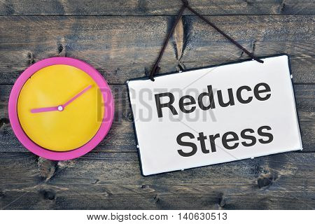 Reduce Stress sign and clock on wooden table