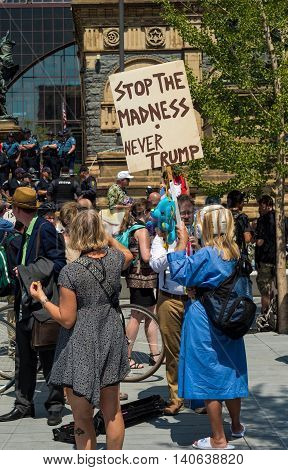 CLEVELAND OH - JULY 20 2016: A protester dressed as a psych-ward patient holds up an anti-Trump sign on Public Square during the Republican National Convention.