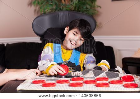Young biracial disabled boy in wheelchair playing checkers at home. Child has cerebral palsy.