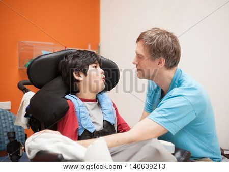 Father talking with disabled biracial son sitting in wheelchair while waiting in doctor's office laughing together.