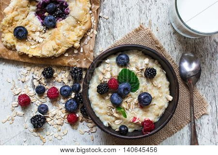 healthy breakfast. oatmeal with ripe berries blueberry cake and glass of milk with a spoon with white wooden background. top view