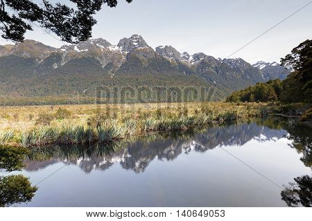 A mirror reflection of mountains in the lake during calm and windless day.