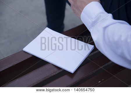 Mockup cover magazine, catalog, book. Man reading a blank magazine, catalog, book on the bench.