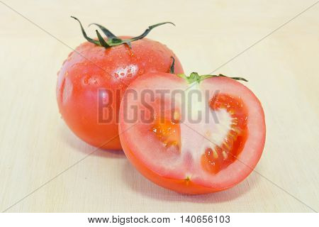 Tomato Fruit With Half Cross Section Isolated On Wooden Background