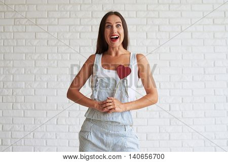 Amazing beautiful brunette dressed in singlet and overalls and hold red paper heart, over white brick wall on background