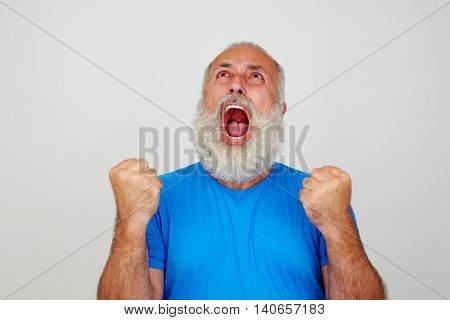 Aged man with white beard is screaming in fury with mouth widely opened and clenched fists isolated against white background