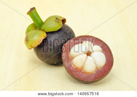 Mangosteen Fruit With Half Cross Section Isolated On Wooden Board