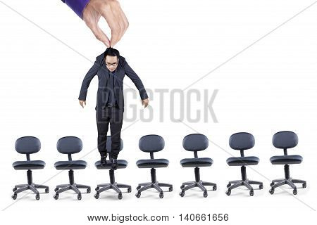 Photo of a hand holding a businessman above the office chairs isolated on white background