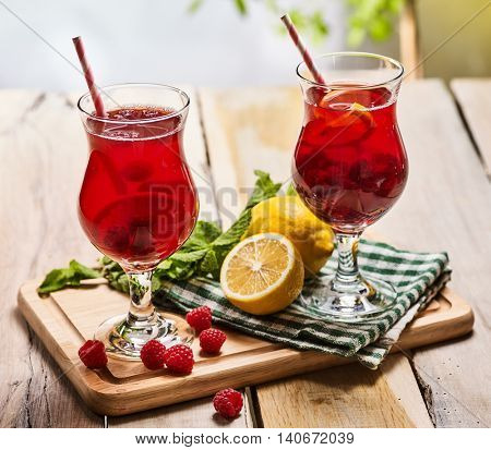 On wooden boards are ice cold beverage two glasses with red berries lemon cocktail . Alcohol country cocktail beverage number three hundred and sixteen with leaf mint. Outdoor cocktail . Sun morning.