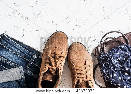 Women's clothing and accessories - suede boots jeans leather bag scarf. On a light background top view