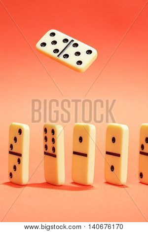 White dominoes standing in a row on red background. One domino above