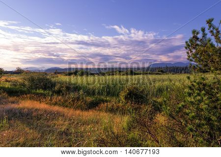 Sunset in countryside valley, blue cloudy sky