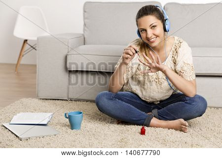 Beautiful woman at home making a pause to painting her nails while listening music