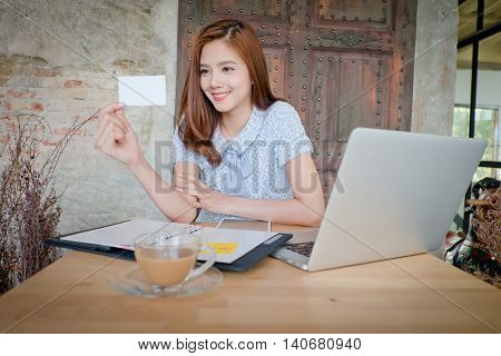The Beautiful Business Woman Using A Laptop Computer,showing Blank Name Card