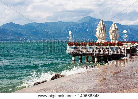 Stormy Garda lake with promenade and closed restaurant in Torri del Benaco Italy