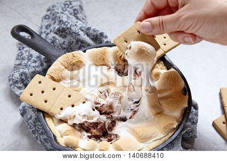 Smores dip baked in a cast iron pan with graham crackers poster