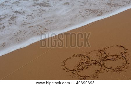 Sydney, Australia - Jul 31, 2016. Wave approaches olympic rings drawn in the sand. Summer Olympic Games Rio 2016.