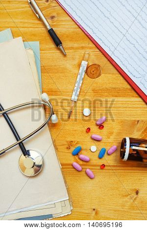 Colorful medical tablets and pills scattered on doctor's office desk top view
