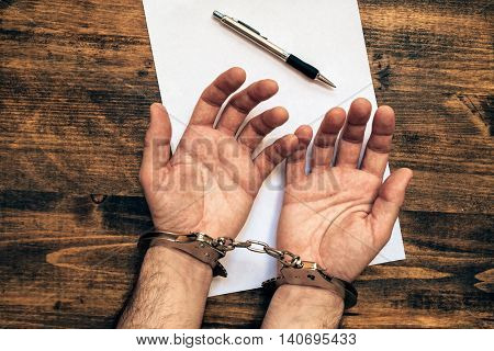 Male hands cuffed top view of police investigator detective desk with pencil and blank paper for statement