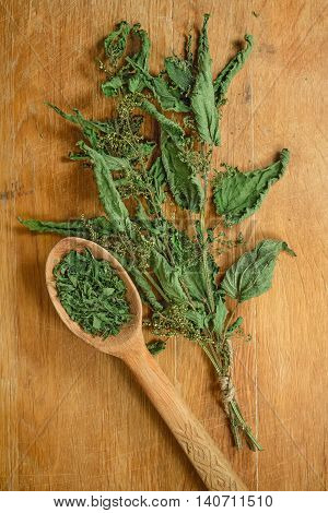 Nettle.Dried herbs for use in alternative medicine.Herbal medicine phytotherapy medicinal herbs.For preparation of infusions decoctions tinctures powders ointments tea. Background wooden board