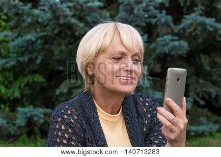 Elderly woman chats by video messenger on cellar phone
