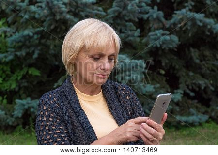 Elderly woman dials or texts on mobile cellar phone