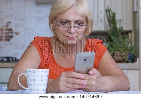 Elderly woman texts sms on cellar phone