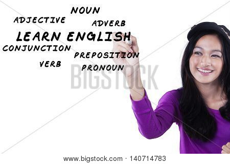 Photo of a beautiful schoolgirl writes English material on the whiteboard isolated on white background