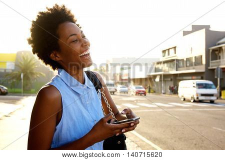 Cheerful Young Woman With Mobile Phone On The City Street