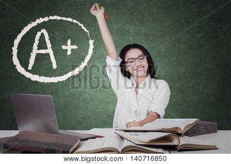 Happy student raising hand with book on the table and grade A plus on the blackboard