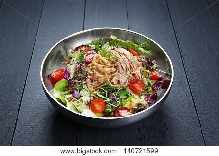 Chichen salad Pasta with spaghetti tomato and herbs in bowl