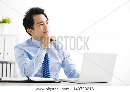 smiling young businessman working on laptop and thinking