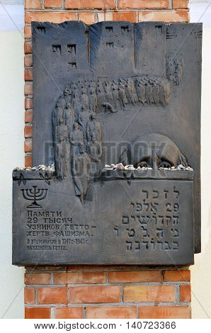 GRODNO, BELARUS - MAY 11, 2016: Monument to the Jewish ghetto victims. A stone plaque with a carved statue of a queue of people. Grodno, Belarus.