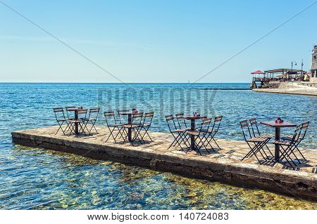 A Row Of Small Tables Of Bars On The Pier