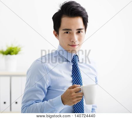 smiling young asian business man drinking coffee