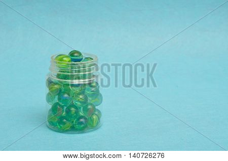 A collection of marbles in a plastic jar displayed on a blue background