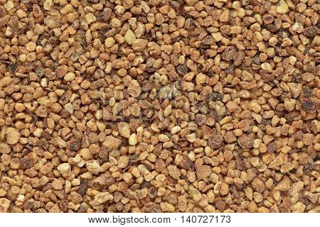Organic Nutmeg (Myristica fragrans) in big cut size. Macro close up background texture. Top view.