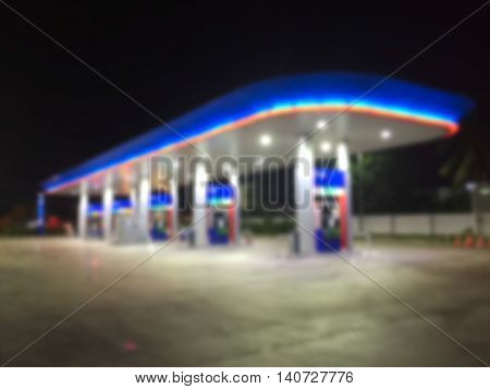 Night light neon gas station on blurry background.