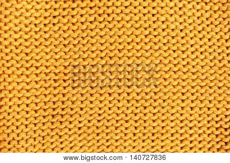 Yellow knitted texture. Wool yarn in knitting background.