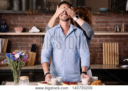 Guess who. Exciting woman closing eyes of his cheerful man while standing in the kitchen at home